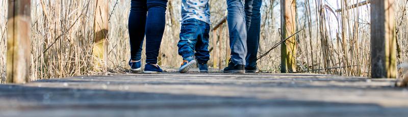 Junge Familie geht über Brücke